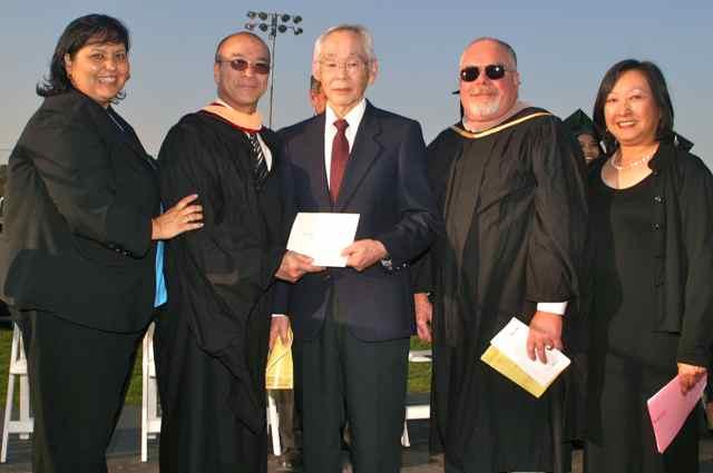 Ken Morishige (center) accepts diploma for Mutsue Uyeno. Manzanar Committee member Colleen Miyano is on the far right. Photo: Mario G. Reyes/Rafu Shimpo.