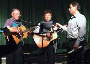 Phil Shigekuni (left) and Nancy Gohata (center) of the San Fernando Valley Japanese American Citizens League perform a musical tribute to Tak Yamamoto
