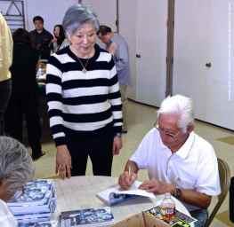 Hank Umemoto autographs a copy of his book for Rose Ochi (left).