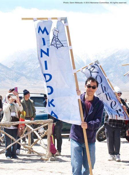 Banners representing all of the American concentration camps during World War II, the Crystal City Internment Camp, and a banner honoring the 100th Battalion/442nd Regimental Combat Team/Military Intelligence Service, are part of each year's Manzanar Pilgrimage. Carrying the Minidoka banner is Michael Okamura.