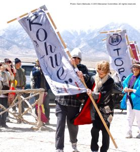 Banners representing all of the American concentration camps during World War II, the Crystal City Internment Camp, and a banner honoring the 100th Battalion/442nd Regimental Combat Team/Military Intelligence Service, are part of each year's Manzanar Pilgrimage. Carrying the Rohwer (with some help) is Ruth Beadles.