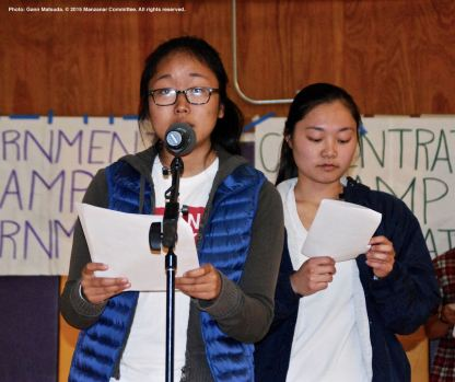 College students organize the Manzanar At Dusk program, which begins with a creative presentation in which portions of actual stories from former incarcerees are portrayed. Shown here are UCSD Nikkei Student Union members Rena Ogino (at the mic) and Kelsey Nakamura (background).