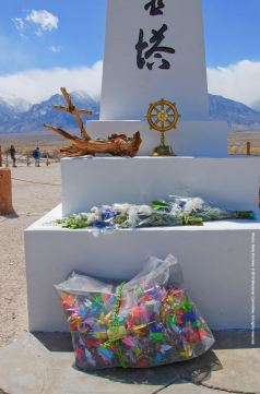Flowers and 1,000 origami cranes, waiting to be draped around the Manzanar cemetery monument.