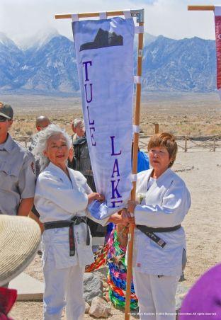 Ernie Jane Nishi (left) and Nancy Oda (right) carried the Tule Lake banner.