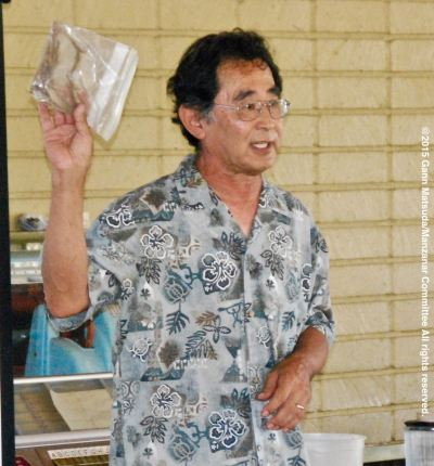 Dr. Glenn H. Kageyama speaking at the program on the Manzanar Guayule Rubber Project, August 30, 2015, Gardena, California. Kageyama is holding samples of rubber made from the Guayule plant.