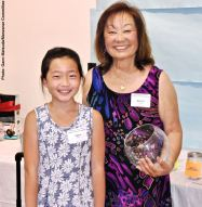 Just the first of the raffle prizes won by Sara Omura (left), shown here with Manzanar Committee member Kerry Cababa
