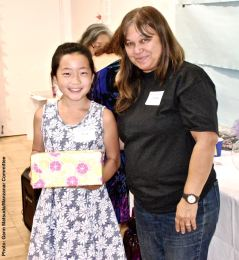 Sara Omura (left) with her third raffle prize win of the day, shown here with Manzanar Committee member Vicky Perez