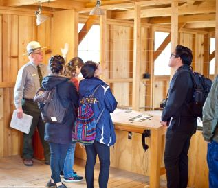 Students listening to Manzanar National Historic Site Ranger Mark Hachtmann discussing living conditions at Manzanar during World War II. This photo was taken inside the Block 14 barrack (1942 conditions).
