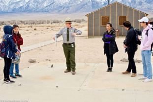 Students with Manzanar National Historic Site Ranger Mark Hachtmann discussing living conditions at Manzanar during World War II. This is the historic foundation for the Block 14 men's latrine.