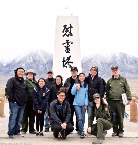 A group photo at the Manzanar cemetery monument at the end of day one. Front (from left): Brian Kohaya, Rose Masters: Back (from left): Jason Fujii, Alisa Lynch, Erica Wei, Bruce Embrey, Moet Kurakata, Gann Matsuda, Lauren Matsumoto, Maru Streets, Mark Hatchmann.
