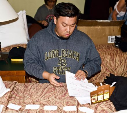 """During the traditional spam musubi making """"party"""" at our headquarters motel, the Dow Villa Motel in Lone Pine on the Friday before he Manzanar Pilgrimage and Manzanar At Dusk events. we also do the prep work for the events. In this photo, Manzanar Committee member Jason Fujii is working on materials for Manzanar At Dusk."""