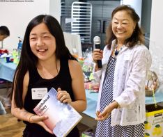Award winner Sara Omura wins one of the raffle prizes. That's Manzanar Committee member Kerry Cababa on the right.