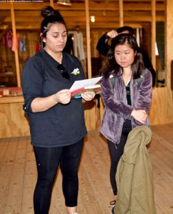 In one of the barracks in Block 14, CSULB Nikkei Student Union member Kylie Castaneda (left) reads an excerpt from an oral history interview with a former Manzanar incarceree.