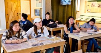 Students listening to a presentation by Ranger Patricia Biggs while seated in the new classroom exhibit at Manzanar.