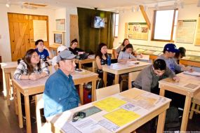 Students and Manzanar Committee Co-Chair Bruce Embrey listening to a presentation by Ranger Patricia Biggs while seated in the new classroom exhibit at Manzanar.
