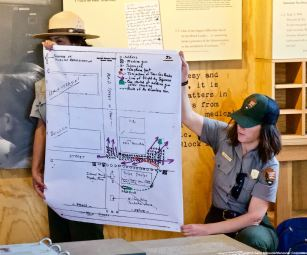 "Manzanar NHS Superintendent Bernadette Johnson (left) and Ranger Rose Masters (right) are shown here with a map/chart of what may have occurred during the Manzanar ""Riot,"" December 5-6, 1942."