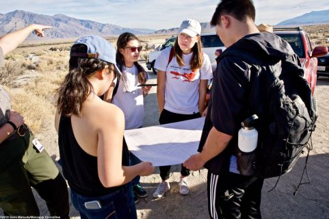 Students looking at a map of what remains at the site of the Manzanar Reservoir.