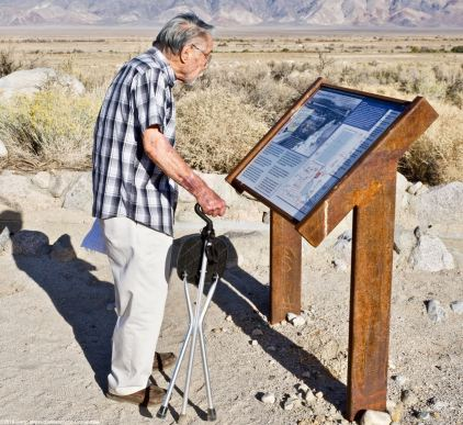 Former Amache incarceree Min Tonai, shown her reading the wayside exhibit at the Manzanar Reservoir.