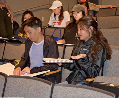 Students look at and discuss archived comment books that visitors to the Manzanar Visitors Center have written in over the years.