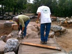 Amos and Robert remove planks from the temporary bridge.