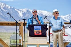 Manzanar Committee Co-Chair Bruce Embrey (center), shown here with Co-emcee Warren Furutani (right), during the 50th Annual Manzanar Pilgrimage, April 27, 2019, at the Manzanar National Historic Site.