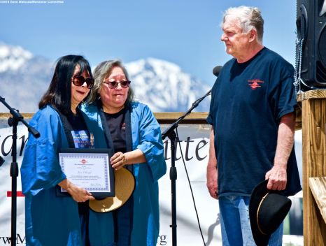 Manzanar Committee members Jenny Chomori (center) and Darrell Warren (right), shown here honoring Manzanar Committee member Joyce Okazaki (left) for her educational work on behalf of the Manzanar Committee, during the 50th Annual Manzanar Pilgrimage, April 27, 2019, at the Manzanar National Historic Site.