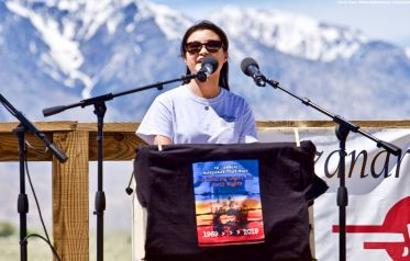 UCSD Nikkei Student Union co-President Lauren Matsumoto (right), addresses the crowd during the 50th Annual Manzanar Pilgrimage, April 27, 2019, at the Manzanar National Historic Site.